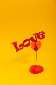 Wooden word love on a yellow background. valentine day concept.