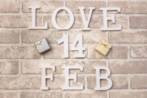 灰色のレンガの背景に木製の言葉「愛」と「2月」。バレンタインデーのデザイン
