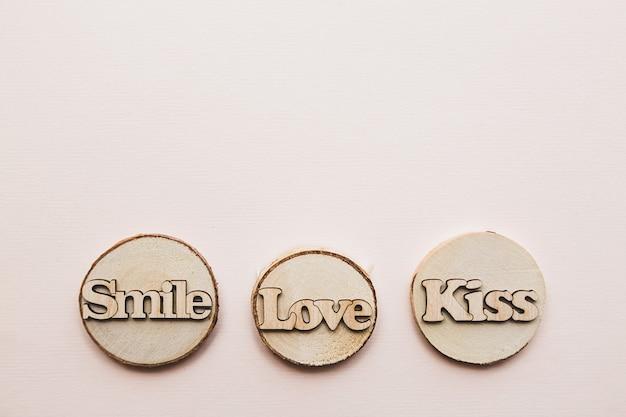 밝은 분홍색 배경에 나무 단어 사랑 키스 미소