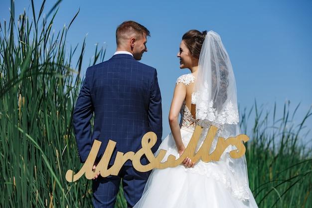 新婚夫婦の手の中に「ミスターとミセス」の木の言葉。晴れた日の自然の中で結婚式の日
