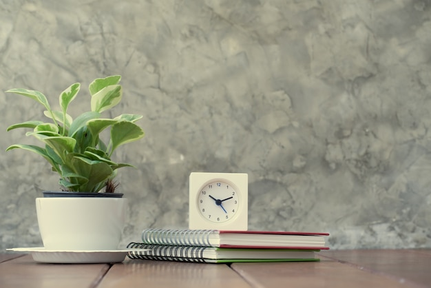 Wooden work table with notebook, alarm clock and fresh green tree in vase pot