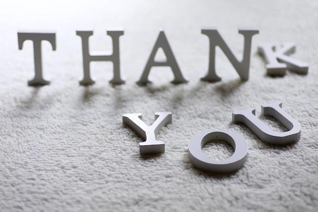 Деревянное белое письмо спасибо на мятом ковре на полу.
