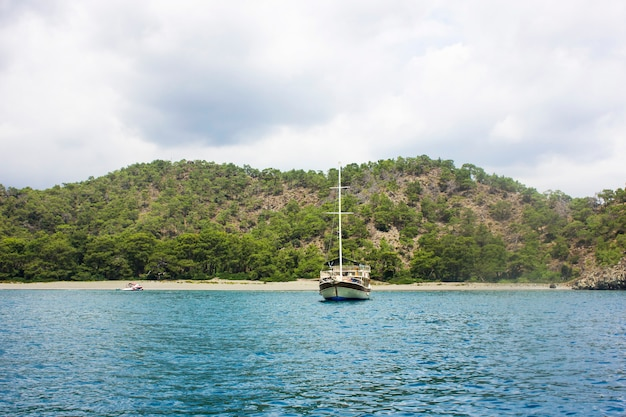 Wooden yacht in the calm blue mediterranean sea in a green lagoon with mountains