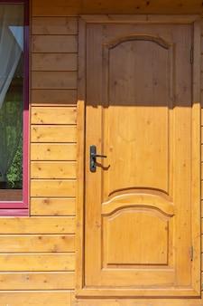 Wooden yellow door with black handle lightened by sun