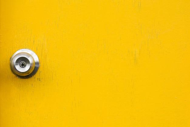 Wooden yellow door with old knob
