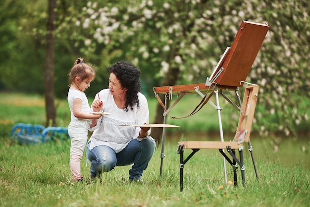 In woods. teaching granddaughter how to paint. in the natural parkland