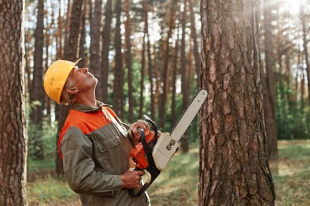 손에 톱을 들고 유니폼과 보호 헬멧을 착용하는 나무꾼