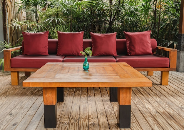 Woodwn table and sofa with red cushion on wooden floor in garden.