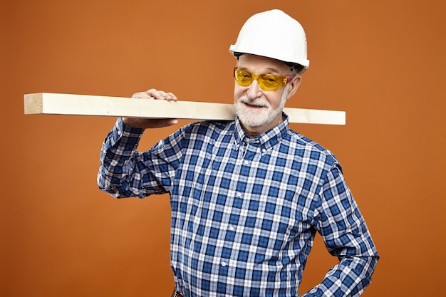 Woodwork, craft and carpentry concept. confident positive senior mature woodman or carpenter with thick beard smiling , carrying wooden plank on his shoulder at blank orange wall