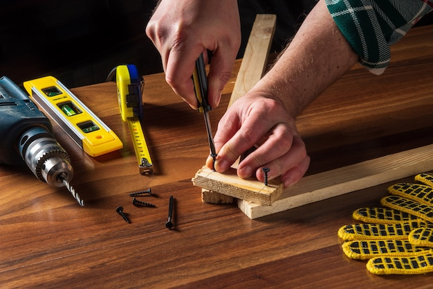 Столяр соединяет деревянные доски отверткой и шурупом.