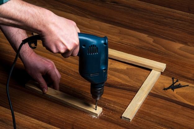 Woodworker는 목재 보드에 전기 드릴로 구멍을 뚫습니다.