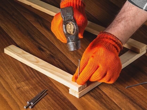 Столяр забивает молотком гвоздь в доску. руки в рабочих перчатках мастера крупным планом. рабочая среда в столярной мастерской