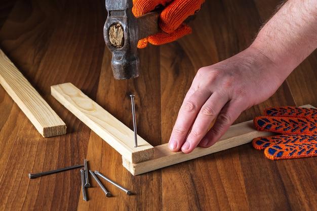 木工職人はハンマーで釘を板に打ち込みます。マスターのクローズアップの手。