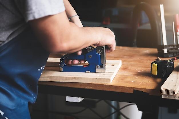 Столяр держит степлер для сборки деревянных деталей по заказу клиента