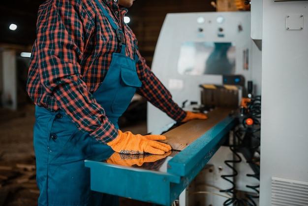 Деревообрабатывающий в униформе и наушниках работает на деревообрабатывающем станке, в деревообрабатывающей промышленности, на столярных изделиях. обработка древесины на заводе