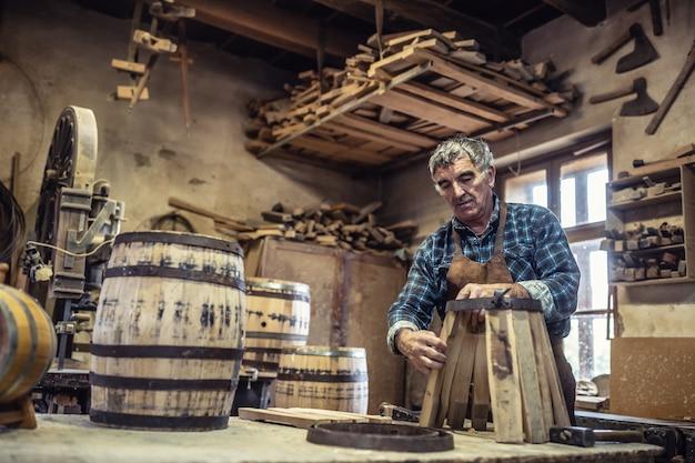 목공은 그의 rusti 작업장에서 수제 나무 통 제조를 위한 목재 기초를 준비합니다.