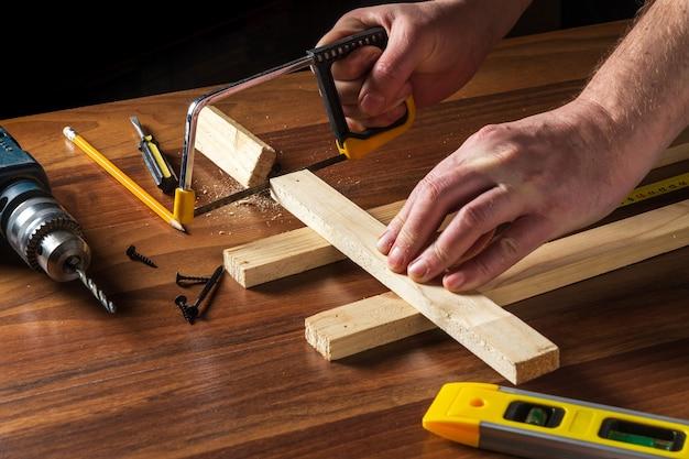 Столяр распиливает деревянную доску. закройте руки мастера на работе.
