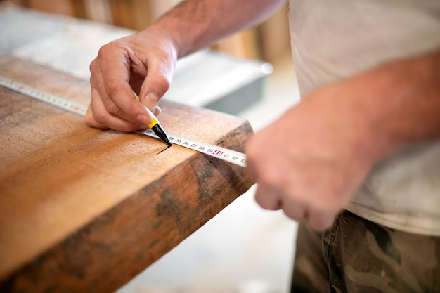 Woodworker taking measurement with a tape