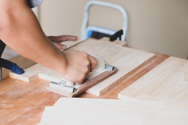 Предприниматели, занимающиеся деревообработкой, используют наждачную бумагу для украшения деревянных деталей, чтобы собрать и построить деревянные столы для своих клиентов.