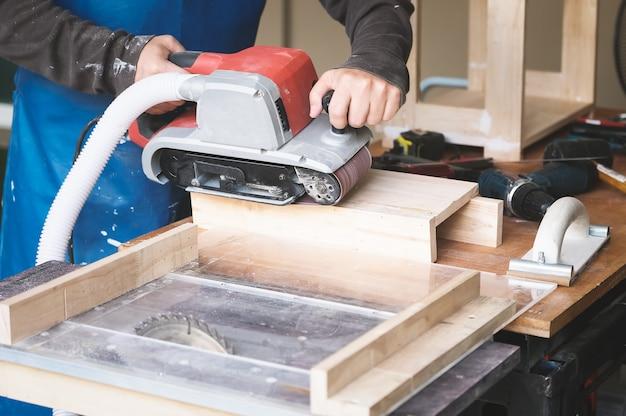 Предприниматели, занимающиеся деревообработкой, используют станки для отделки наждачной бумагой для сборки и изготовления деревянных столов для своих клиентов.