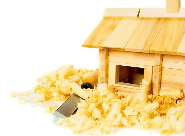 木工。住宅建設。ジョイナーの作品。小さな木造家屋、ノミ、飛行機、白い背景のシェービング。