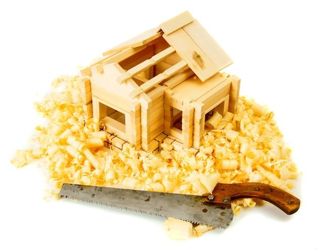 木工。住宅建設。ジョイナーの作品。小さな木造家屋、白い背景に鋸とひげそり。