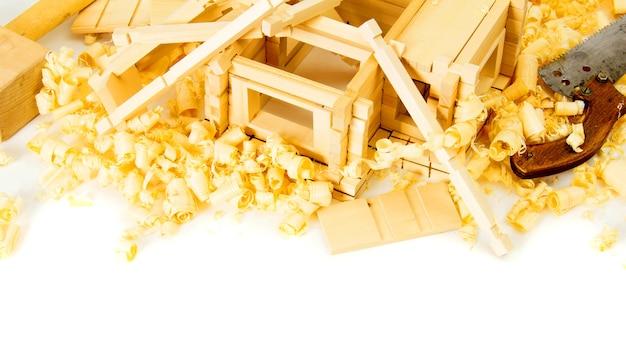 木工。住宅建設。ジョイナーの作品。小さな木造家屋、のこぎり、飛行機、白い背景のシェービング。