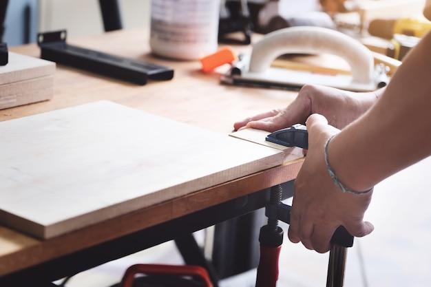 Операторы по деревообработке украшают куски дерева, чтобы собрать и построить деревянные столы для клиентов.