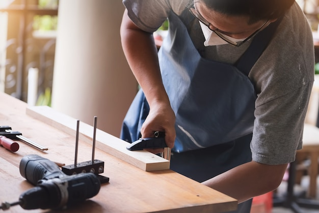 Операторы по деревообработке украшают куски дерева, чтобы собрать и построить деревянные столы для клиентов. Premium Фотографии