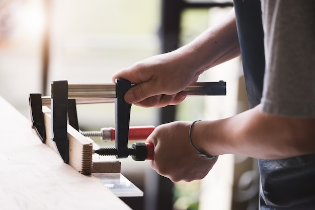 Woodworking operators are decorating pieces of wood to assemble and build wooden tables for customers