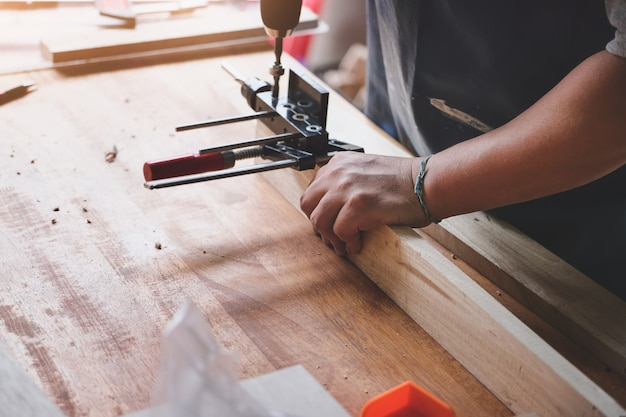 Woodworking operators are using a drill to drill holes in wood to assemble and build wooden tables for customers