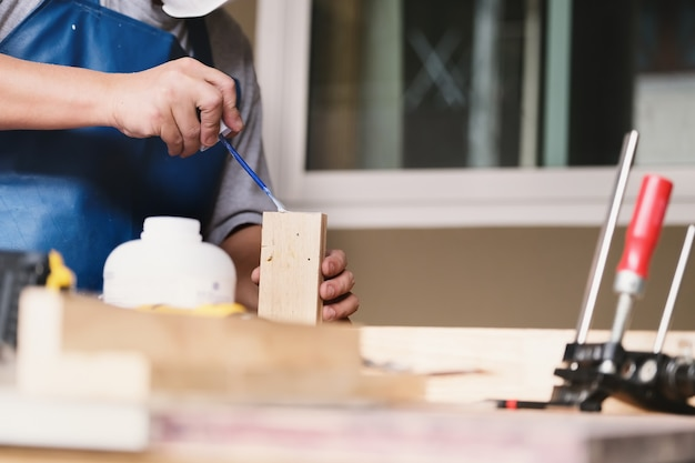 Woodworking operators are using glue to put together the wood parts to assemble and build a wooden table for their customers