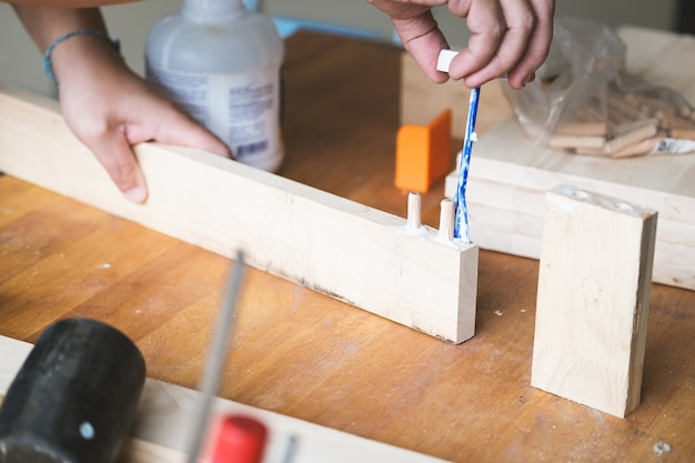 Операторы деревообработки используют клей, чтобы собрать деревянные детали, чтобы собрать и построить деревянный стол для своих клиентов.