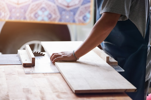 Woodworking operators are using plank cutting machines to assemble and build wooden tables for customers
