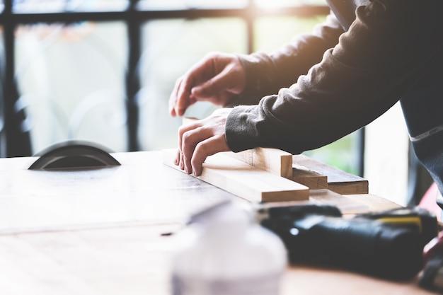 Практики деревообработки используют полотна пил, чтобы вырезать деревянные части, чтобы собрать и построить деревянные столы для своих клиентов.