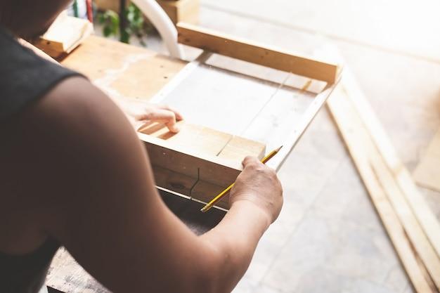 목공 종사자는 톱날을 사용하여 나무 조각을 자르고 고객을 위해 나무 테이블을 조립하고 만듭니다.