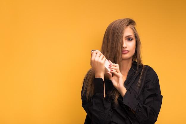 Портрет красивой девушки с телефоном wooku на желтой предпосылке. эмоция была вдумчивой.