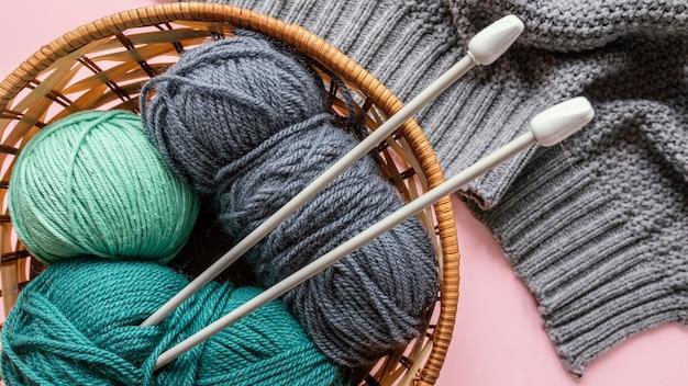 바구니에 양모와 뜨개질 바늘