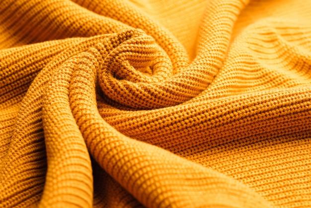 ウールの背景。抽象的な新鮮なカラフルな黄色のニット