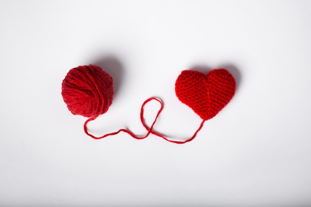Wool ball and heart shape on white background