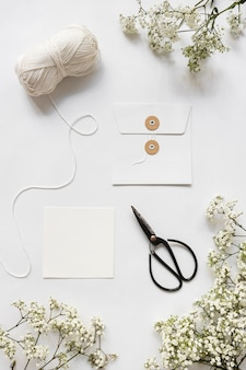 Wool ball; scissor; envelope and baby's-breath flowers on white background