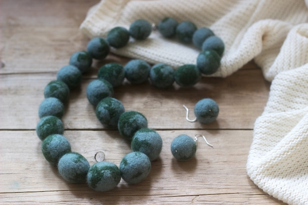 Wool jewelry against the background of a pullover or sweater, felting.