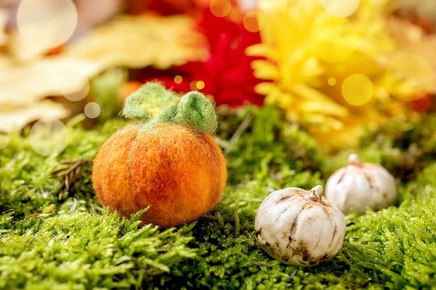 Шерстяное валяние тыква хэллоуина на мхе. осеннее сезонное приветствие хэллоуина