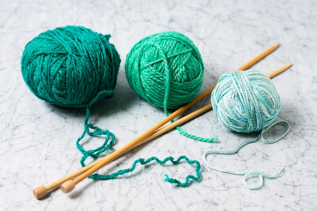 Wool and needles for knitting on table