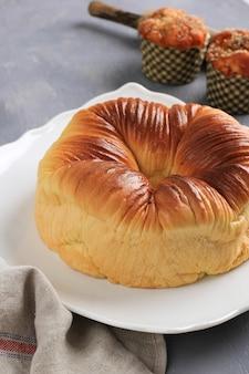 ウールロールパン、ウールのような美しい食感の自家製バイラル日本のブリオッシュミルクパン。背景にマフィンを添えた白いプレートでお召し上がりいただけます。パン屋の素朴なコンセプト