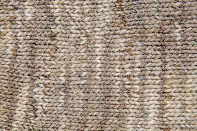 Wool scarf texture close up. knitted jersey background with a relief pattern. braids in machine knitting pattern