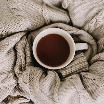 울 스웨터, 니트 격자 무늬 및 커피 컵. 침대에서 아침 식사. 편하고 달콤한 집. 평평한 평신도, 정물