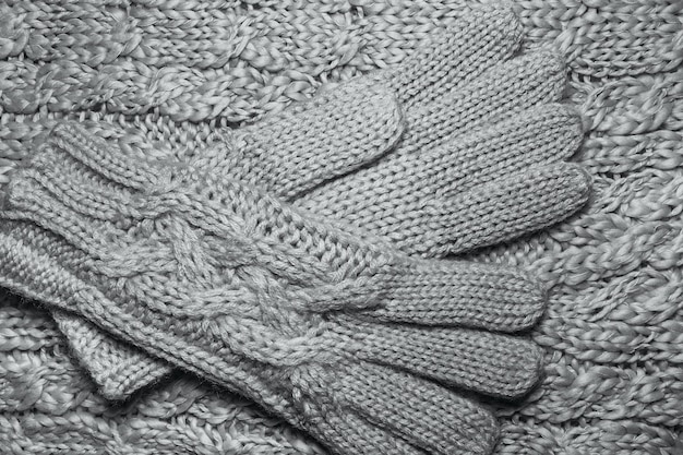 Wool sweater or scarf and gloves texture close up. knitted jersey background with a relief pattern. braids in machine knitting pattern.