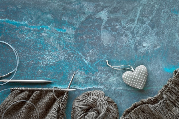 Wool yarn and knitting needles, creative knitting background in blue turquoise with copy space