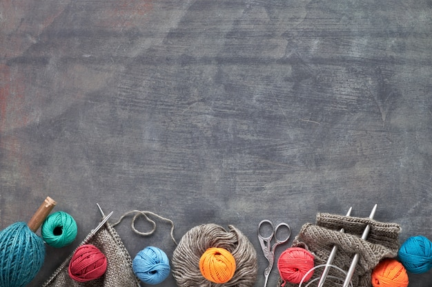 Wool yarn and knitting needles, dark creative knitting background  with copy space